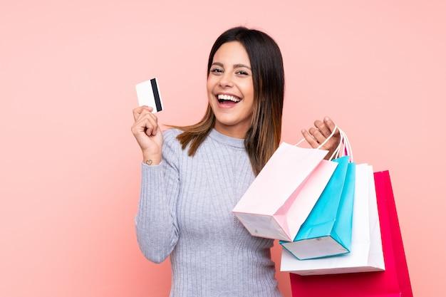 Vrouw over roze muur met boodschappentassen en een creditcard
