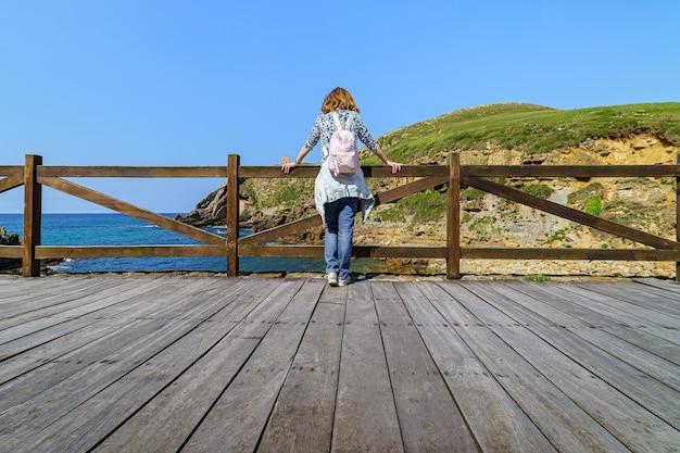 Vrouw overweegt de zee vanaf een houten buitenbalkon santander spanje