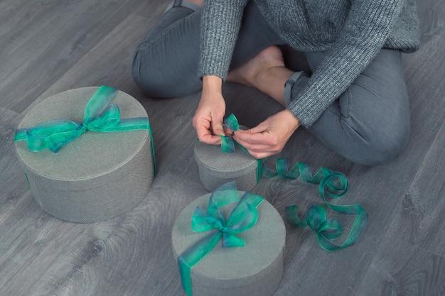Vrouw pack geschenken met grijze ronde dozen en groen lint