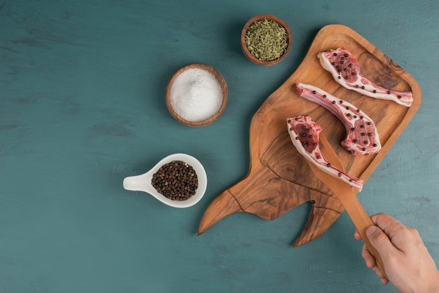 Vrouw pakt een stuk ongekookt vlees van een houten plank.