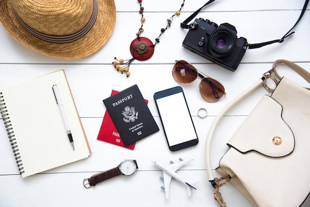 Vrouw. paspoorten, de kosten van reiskaarten die zijn voorbereid voor de reis op een witte houten vloer