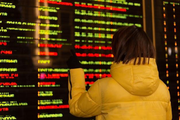 Vrouw passagier op treinstation, bord met vertrekroutes