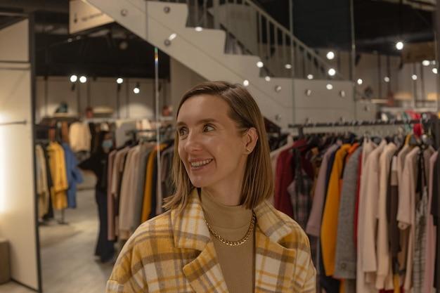 Vrouw past een jas in een paskamer van een kledingwinkel