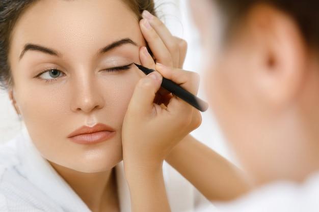 Vrouw past eyeliner toe