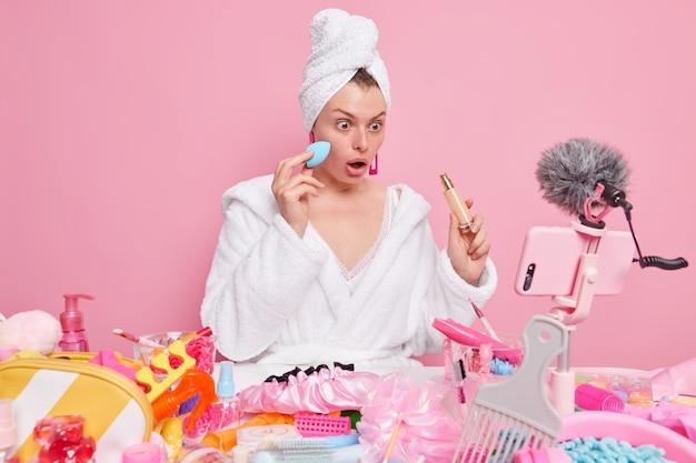 Vrouw past foundation toe staart naar smartphone camera neemt instructievideo op voor beautyblog gekleed in witte badjas en handdoek op hoofd adverteert cosmetische producten.