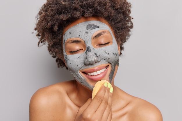 Vrouw past kleimasker toe met cosmetische spons glimlacht zachtjes geniet van huidverzorgingsprocedures sluit ogen van plezier poseert naakt binnenshuis. schoonheidsconcept.