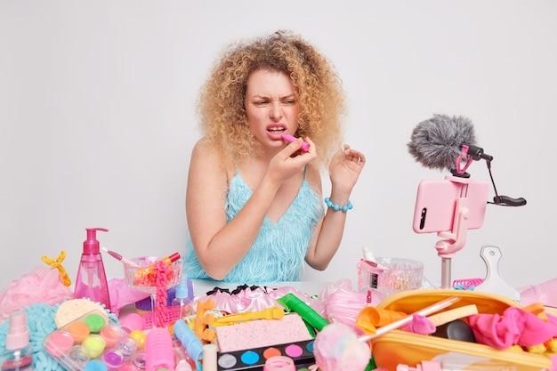 Vrouw past lippenstift toe draagt blauwe jurk zit aan tafel met cosmetische producten rond geïsoleerd op wit
