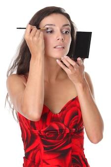 Vrouw past make-up toe - geïsoleerd op wit