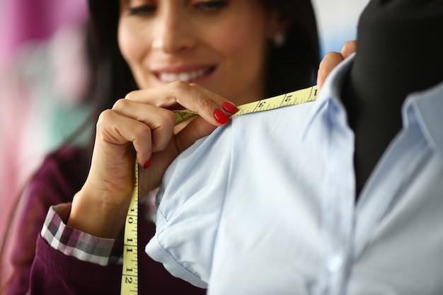 Vrouw past meetlint toe op schoudernaad