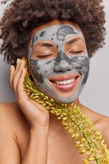 Vrouw past natuurlijke zelfgemaakte klei kruiden gezichtsmasker houdt ogen gesloten raakt gezicht geniet van zachtheid van huid staat alleen shirtless. schoonheid en cosmetologie