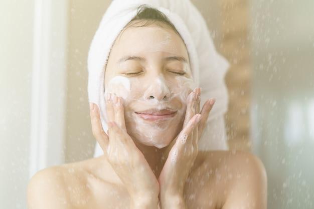 Vrouw past schuimende reiniger toe, schone gezonde huid.