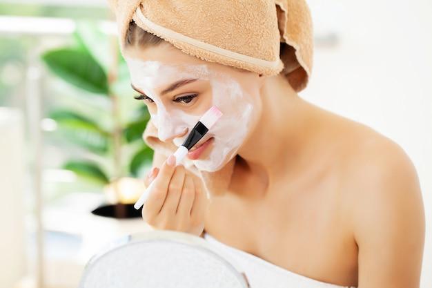 Vrouw past witte kleimasker toe voor gezichtsverzorging in de luxe badkamer van het hotel