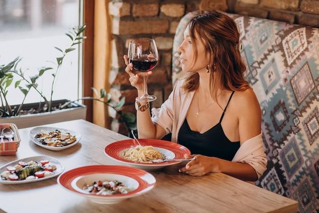 Vrouw pasta eten in een italiaans restaurant