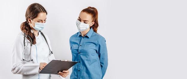 Vrouw patiënt bij arts in maskers bij receptie om de gezondheid te controleren op witte geïsoleerde achtergrond