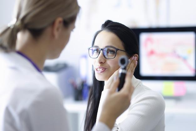 Vrouw patiënt met oor in de buurt van arts met otoscoop in hand in kliniek