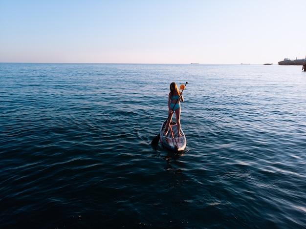 Vrouw peddelen op sup board en genieten van turkoois transparant water.