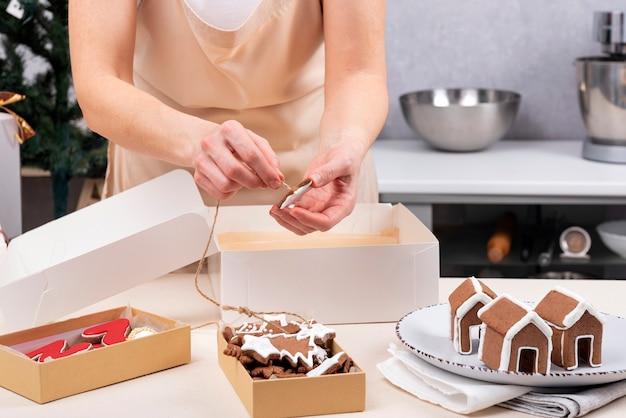 Vrouw peperkoek kerstkoekjes verpakken in vakantie dozen.