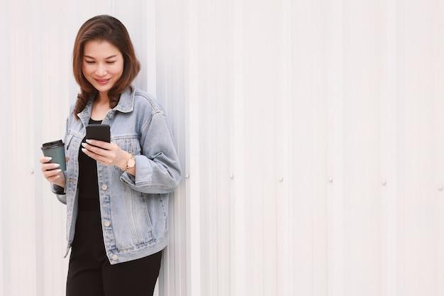 Vrouw permanent en gebruikend smartphone.