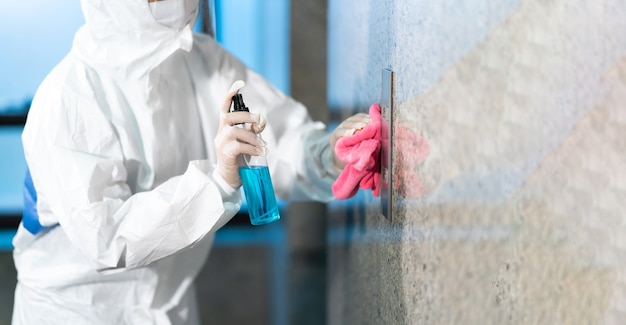 Vrouw personeel werken in hazmat pakken met behulp van veeg schoonmaken van een bedieningspaneel van de drukknop van de lift met een blauwe fles ontsmettingsmiddel