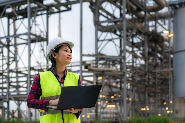 Vrouw petrochemische ingenieur die 's nachts met laptop werkt