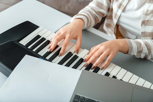Vrouw piano opnemen muziek spelen op synthesizer met behulp van notities en laptop. vrouwelijke handen muzikant pianist verbetert vaardigheden piano spelen. online muziekonderwijs hobby zang zingen met piano.
