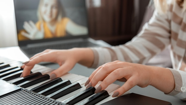 Vrouw piano spelen tijdens videogesprek via laptop. vrouwelijke handen muzikant pianist verbetert vaardigheden door online pianolessen te spelen met leraar. online muziekonderwijs. lange webbanner.