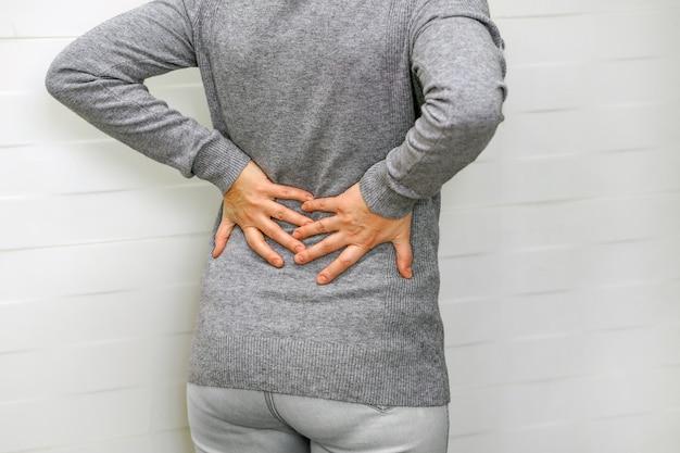 Vrouw, pijn in de onderrug. gezondheidszorg concept.