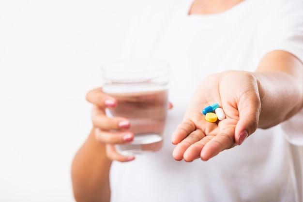 Vrouw pil drugs in de hand houden klaar medicijnen nemen met een glas water