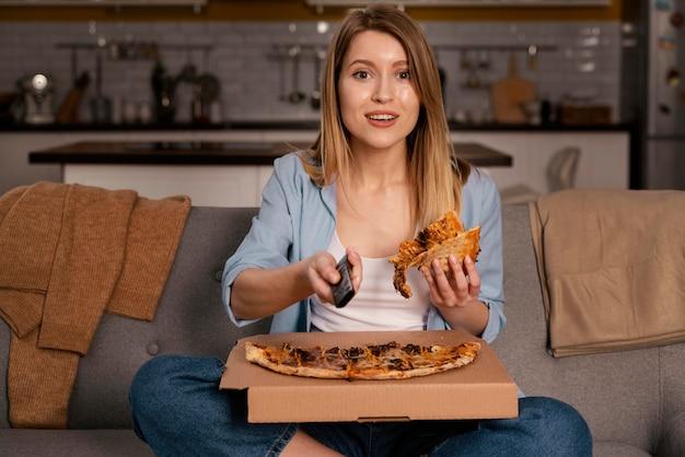 Vrouw pizza eten tijdens het kijken naar tv