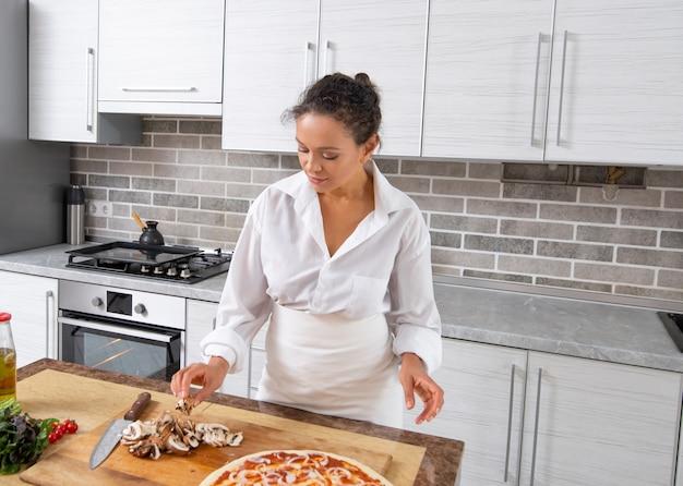 Vrouw pizza thuis koken