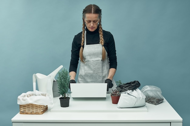Vrouw plant kamerplanten en bloemen in aarde en potten