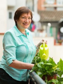 Vrouw planten op balkon water geven