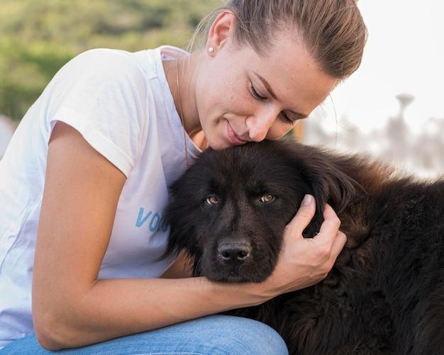 Vrouw pluizige zwarte hond buitenshuis aaien
