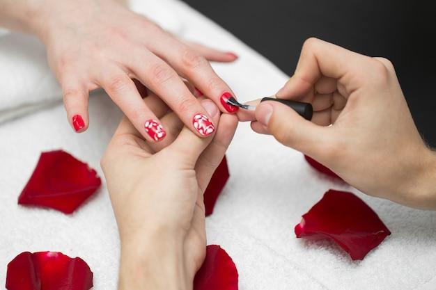 Vrouw poetst haar nagels met rode nagellak in een schoonheidssalon