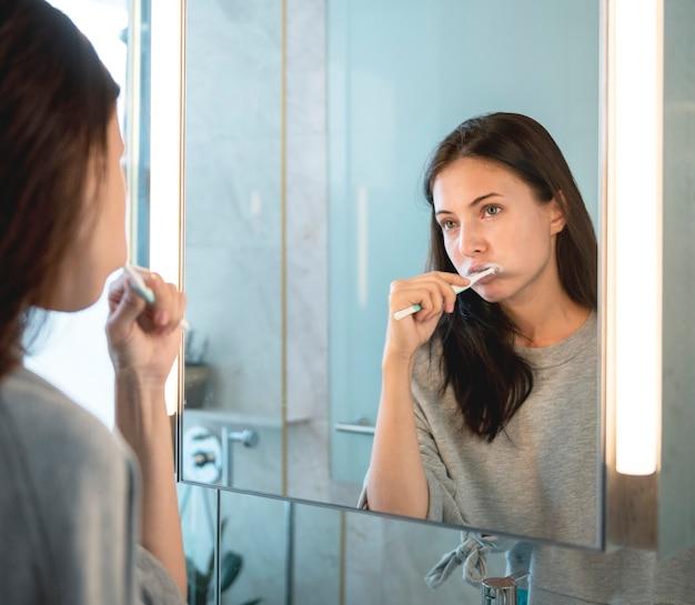Vrouw poetst haar tanden in de ochtend
