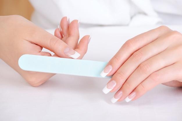 Vrouw polijst haar duim met behulp van de nagelvijl