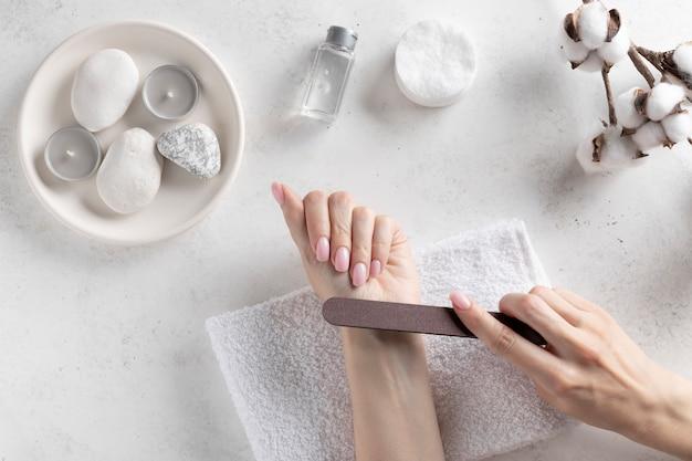 Vrouw polijst vingernagels met de nagelvijl, maakt een gelijkmatige vorm van nagels. nagelverzorging concept. witte betonnen muur. bovenaanzicht. plaats voor tekst