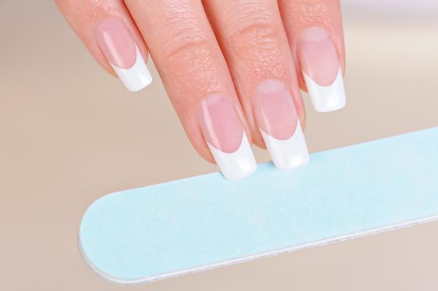 Vrouw polijsten vingernagels bij de hand met nailfile