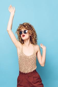 Vrouw portret curly haired zonnebril houdt een hand boven het hoofd van het shirt van mod pailletten
