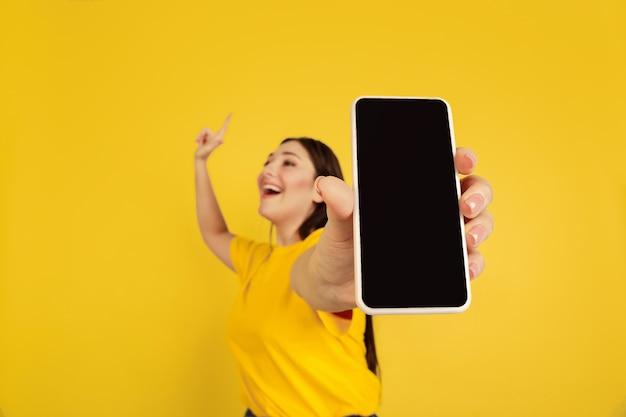 Vrouw portret geïsoleerd op gele studio muur