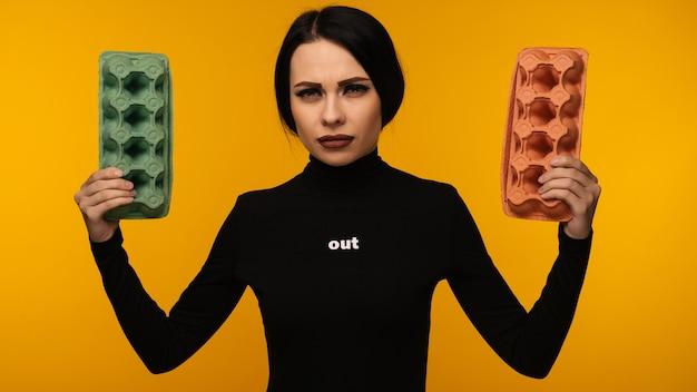 Vrouw portret houden kartonnen doos geïsoleerd op gele achtergrond. het concept van milieuvervuiling door menselijke afvalproducten.
