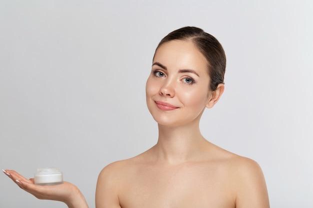 Vrouw portret, huid zorg concept, mooie huid en handen vasthouden en hydraterende crème toepassen. gezichtsbehandeling. cosmetologie, schoonheid en spa.