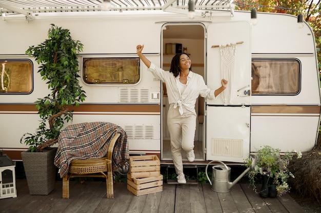 Vrouw poseert bij de ingang van de camper, kamperend in een aanhangwagen. stel reist op busje, vakanties op camper, camper vrije tijd in kampeerauto