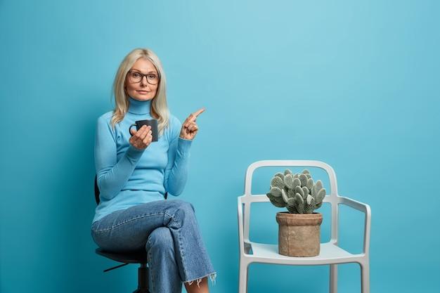 Vrouw poseert in kantoor op comfortabele stoel wijst weg op lege ruimte heeft koffiepauze