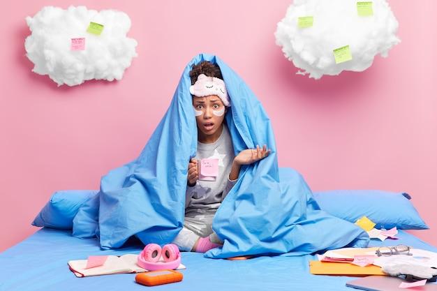 Vrouw poseert onder deken maakt zich zorgen opgewonden uitdrukking vanwege deadline drankjes verfrissend drankje zit gekruiste benen draagt pyjama bereidt projectwerk voor doet thuisopdracht