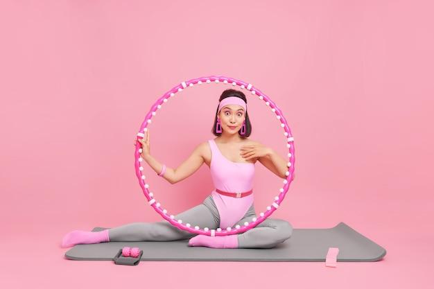 Vrouw poseert op fitnessmat met hoelahoep en andere sportuitrusting doet rekoefeningen heeft thuis sporttraining