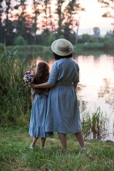 Vrouw poseren buiten in de natuur met een boeket bloemen en genieten van het prachtige uitzicht op het meer en de zon.