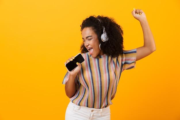 Vrouw poseren geïsoleerd over gele ruimte luisteren muziek met koptelefoon dansen zingen.