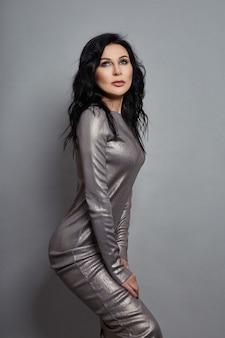 Vrouw poseren gekleed in een grijze jurk