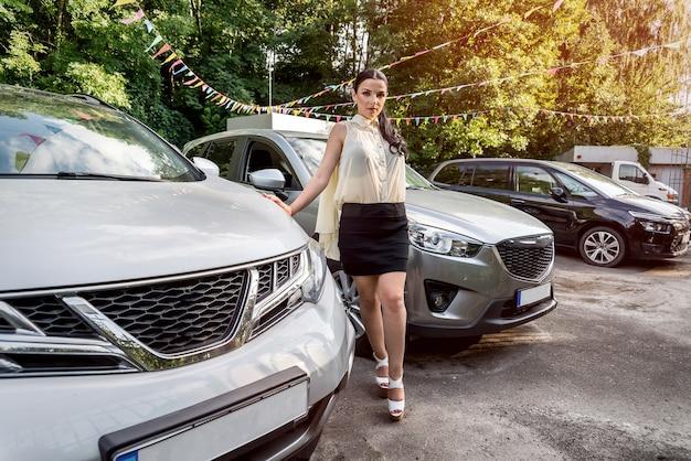 Vrouw poseren in de buurt van nieuwe auto's op parkeerplaats